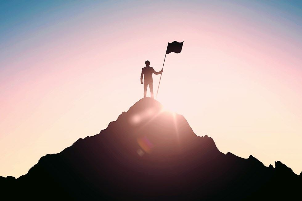 Man on top of a mountain with flag